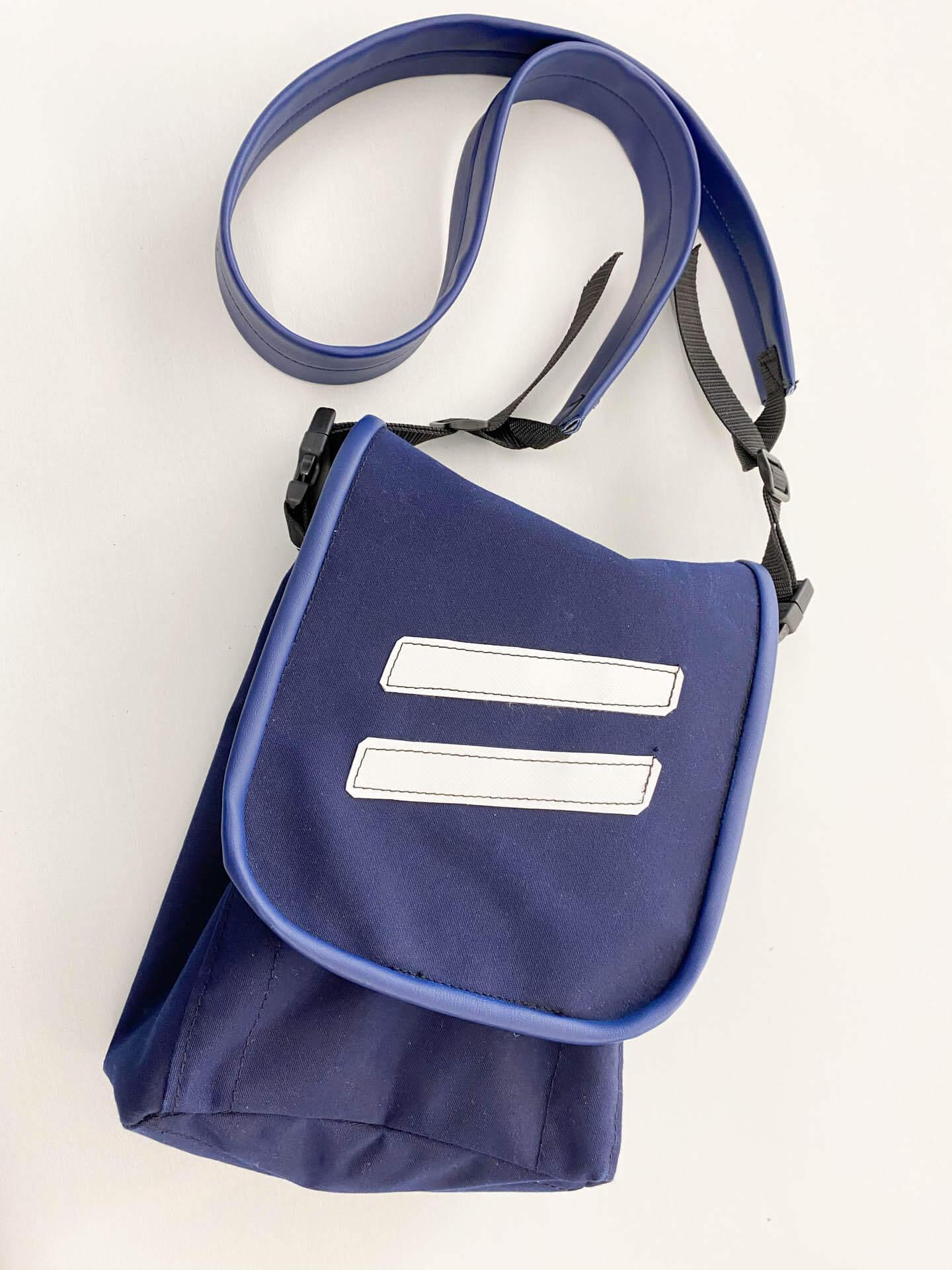 Blaue Umhängetasche mit weißen Streifen und Gurt